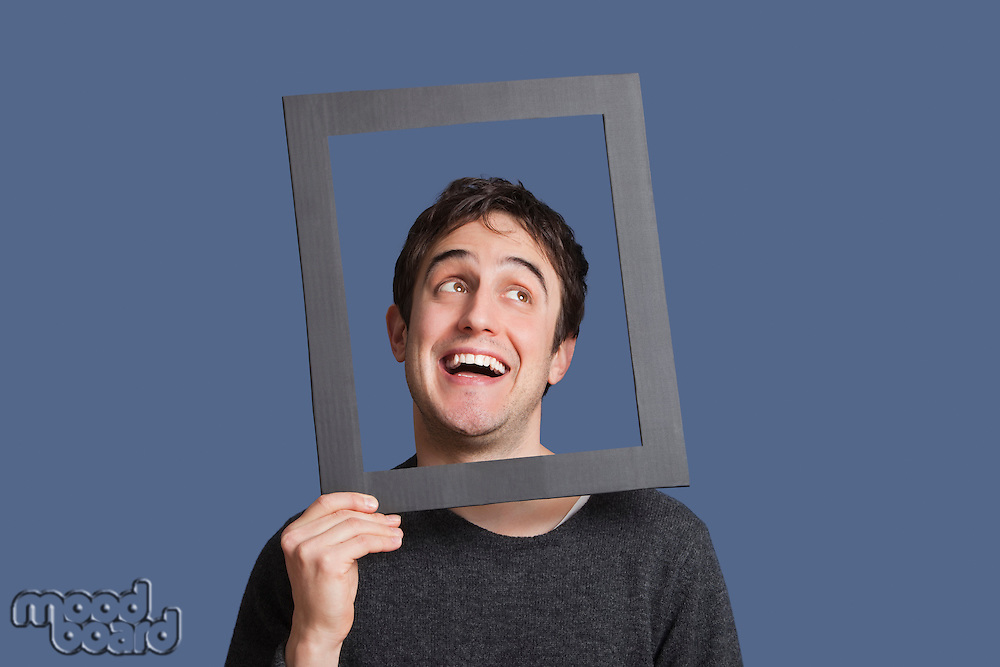 Young man laughing through frame over blue background