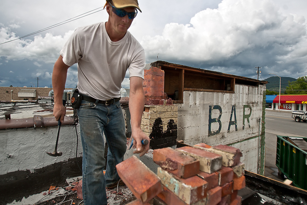 Contractor Tony Martin removes chimney bricks from the roof of the 4th St. Bar during its demolition. After beginning demolition of the building began, Martin and others discovered a great deal of history hidden beneath the layers of older eateries and bars over the years.