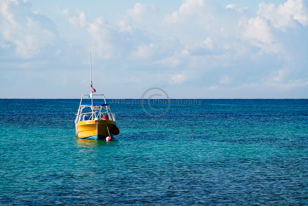 A boat moored off shore in the Caribbean ocean.