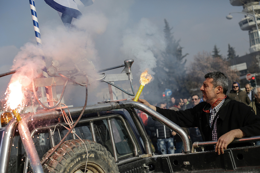 A farmer places a smoke canister in a car during a march inside the city of Thessaloniki, Greece, on the 2nd of February 2017. Farmers from around northern Greece gathered in Thessaloniki during the opening of the Zootechnia international livestock to demonstrate against the austerity measures put by the Greek government.