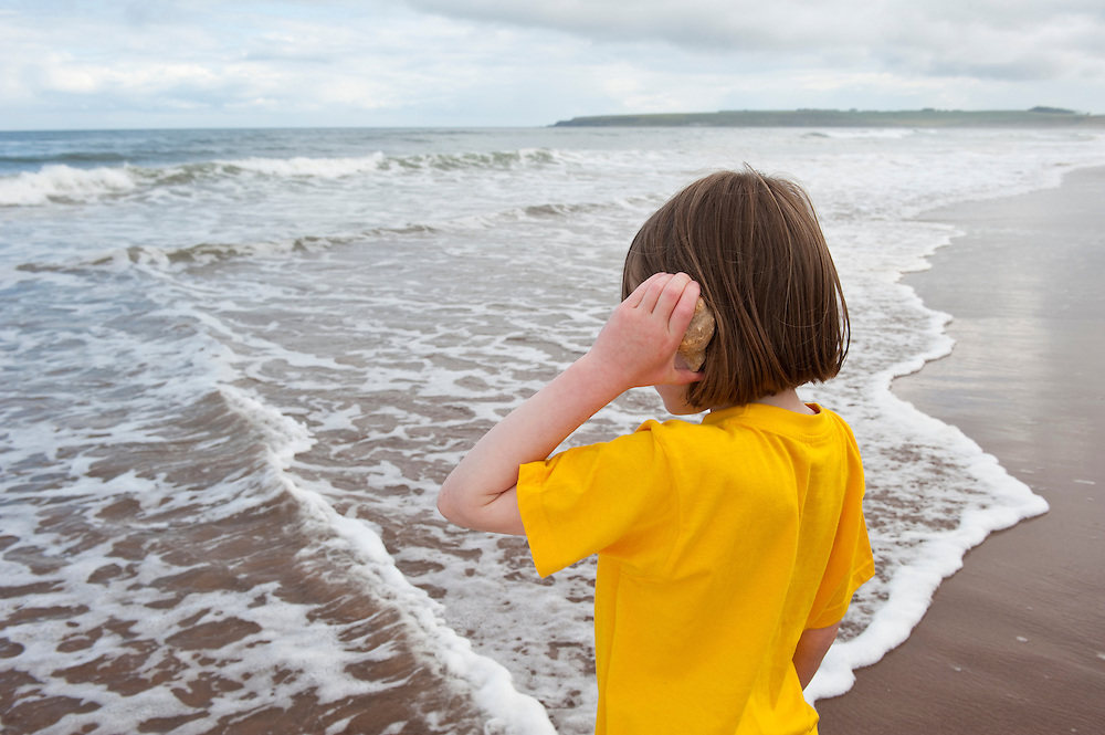 Girl listening to a shell  on the beach, Scotland