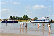 Nederland, Nijmegen, 3-7-2015Warme zomerse dag op het Waalstrand van Nijmegen in de Ooijpolder, makkelijk te bereiken via de voetgangersbrug Ooijblik die hier ligt. Het zwemmen in de rivier de waal, rijn, is gevaarlijk vanwege de veraderlijke stroming en de drukke scheepvaart. Als een grote zesbakscombinatie langs nijmegen vaart begeleidt de politieboot deze langs de strandjes om te zorgen dat er geen zwemmers te dicht bij het schroefwater komen.Foto: Flip Franssen/Hollandse Hoogte