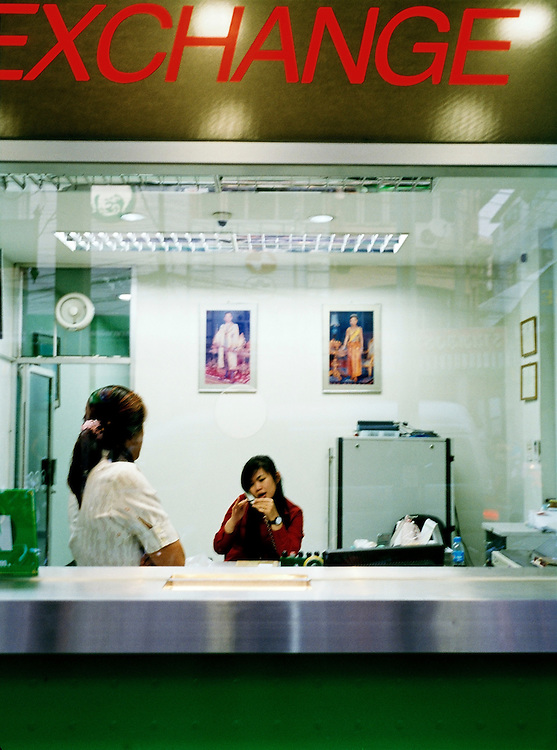 Woman chatting on the phone at a currency exchange.