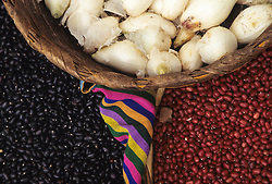Guatemala, Antigua. Close up of beans and onions in a basket at the market.