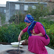 A woman tends to the baking bread in an outdoor stone oven, Nokhur village, Turkmenistan