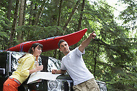 Couple with map on car bonnet in forest man pointing