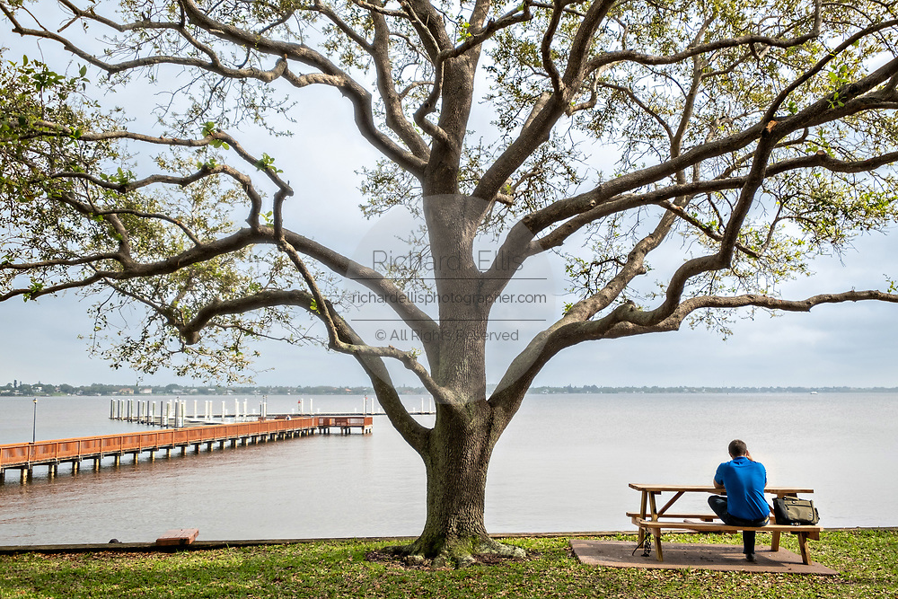 A man sits along the Stuart Boardwalk at Flagler Park in the historic downtown in Stuart, Florida. The tiny hamlet was founded in 1870 and was voted the Happiest Seaside Town in America by Coastal Living.