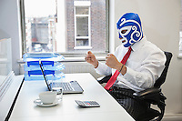 Young businessman celebrating victory in wrestling mask at office desk