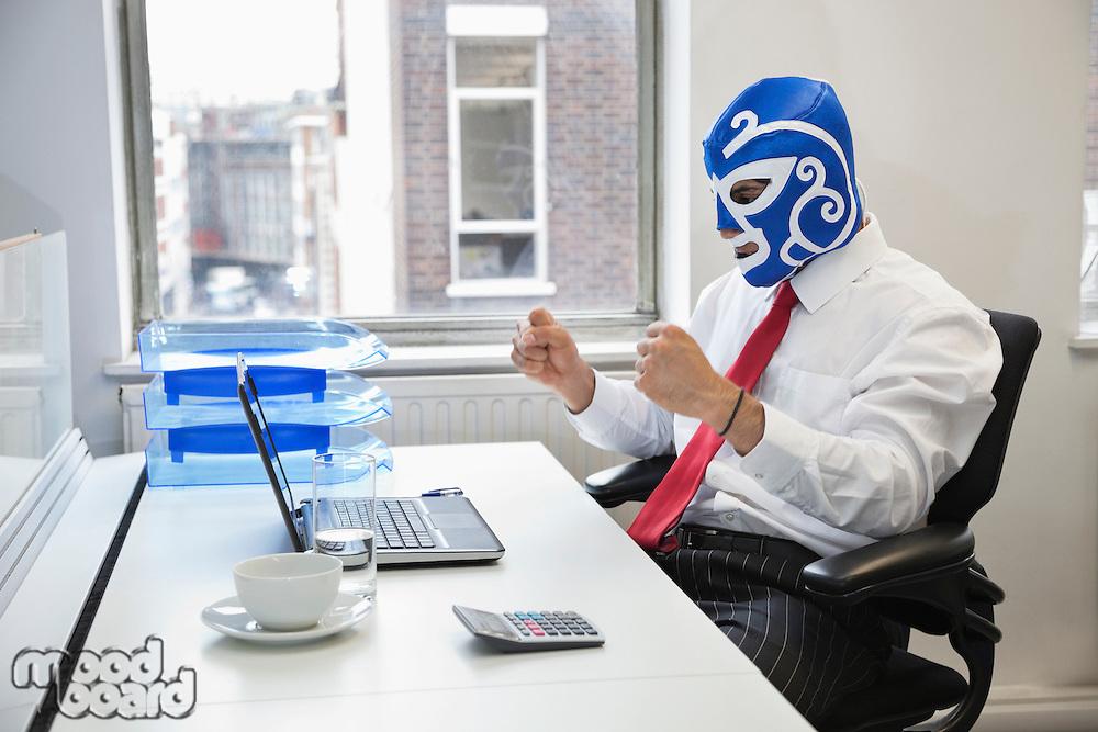 Young businessman celebrating victory in wrestling mask at office desk