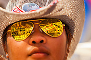 "13 JANUARY 2014 - BANGKOK, THAILAND: The main anti-government stage is reflected in the sunglasses of a protestor near MBK shopping center in Bangkok. Tens of thousands of Thai anti-government protestors took to the streets of Bangkok Monday to shut down the Thai capitol. The protest was called ""Shutdown Bangkok"" and is expected to last at least a week. The Shutdown Bangkok protest is a continuation of protests that started in early November. There have been shootings almost every night at different protests sites around Bangkok, including two Sunday night, but the protests Monday were peaceful. The malls in Bangkok stayed open Monday but many other businesses closed for the day and mass transit was swamped with both protestors and people who had to use mass transit because the roads were blocked.    PHOTO BY JACK KURTZ"