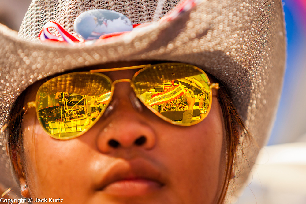 """13 JANUARY 2014 - BANGKOK, THAILAND: The main anti-government stage is reflected in the sunglasses of a protestor near MBK shopping center in Bangkok. Tens of thousands of Thai anti-government protestors took to the streets of Bangkok Monday to shut down the Thai capitol. The protest was called """"Shutdown Bangkok"""" and is expected to last at least a week. The Shutdown Bangkok protest is a continuation of protests that started in early November. There have been shootings almost every night at different protests sites around Bangkok, including two Sunday night, but the protests Monday were peaceful. The malls in Bangkok stayed open Monday but many other businesses closed for the day and mass transit was swamped with both protestors and people who had to use mass transit because the roads were blocked.    PHOTO BY JACK KURTZ"""