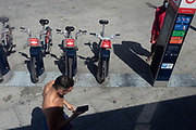 Walking past a line of Santander rental bikes, a shirtless man uses his phone at Elephant & Castle, on 31st July 2020, in London, England.
