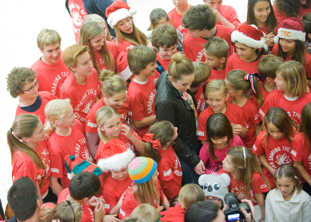 """Miley Cyrus is surrounded by young volunteers at the Sharing the Spirit Holiday Party held for Orange County's shelter and motel kids at South Coast Plaza on Friday night. """"I don't just stop at one thing that's important to me,"""" she told the kids in urging them to keep volunteering to help others in their communities. """"Whatever makes you happy, that's what you give."""""""