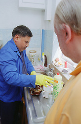 Male carer washing up wearing rubber gloves at kitchen sink,