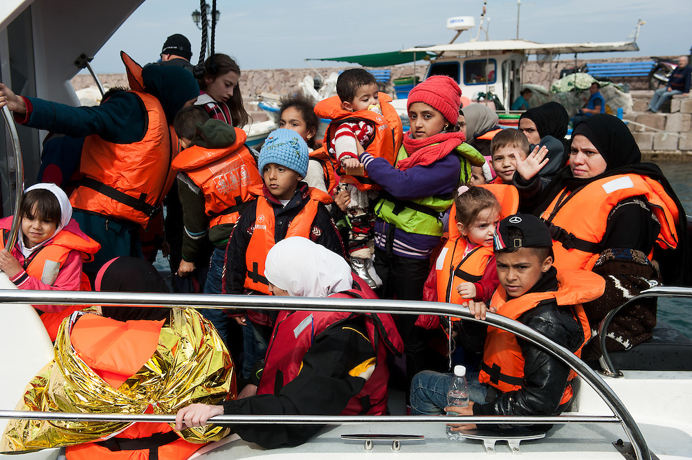 A Portuguese coast guard vessel  that was towing a dinghy with around 50 refugees is docking at the fishing harbour of  Skala Sykamias, Lesvos, Greece