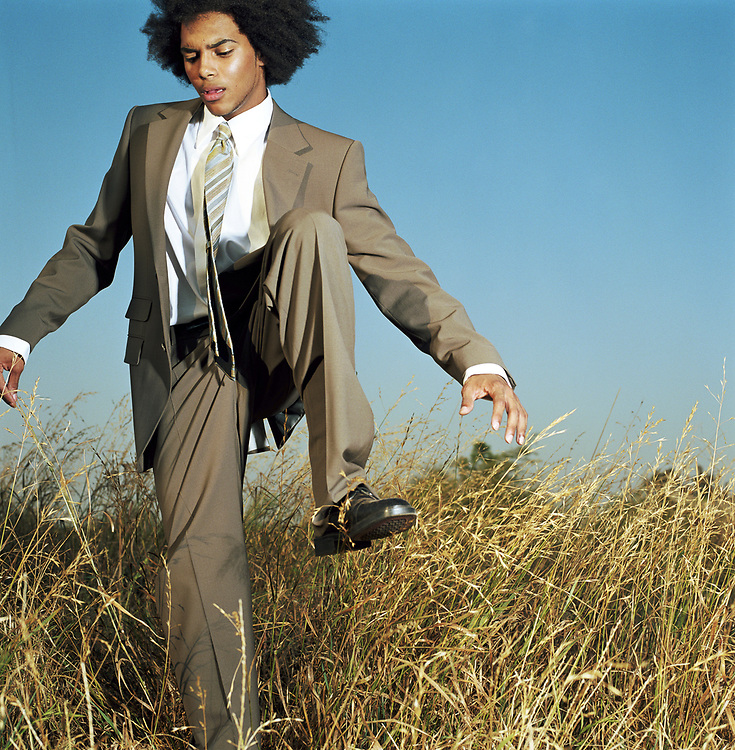 Young man wearing business suit, stepping through field