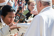 A Woman Kisses Pope Francis hand  upon his arrival in St. Peter's square at the Vatican for his weekly general audience on March 14, 2018.