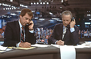 Peter Jennings, (with cigarette on table next to his script, and David Brinkley talk  on telephones in the ABC booth at the Democratic Convention in San Francisco, CA in July 1984..Photograph by Dennis Brack bs b 17