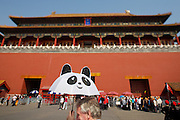 Gugong (Forbidden City, Imperial Palace). Tourists and tour groups cueing in front of Wumen (Meridian Gate). Foreign tourist with Panda umbrella.