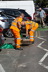 Workers clear up the debris following a high speed crash involving two high performance cars on Chiselhurst High Street in South East London. London, August 22 2019.