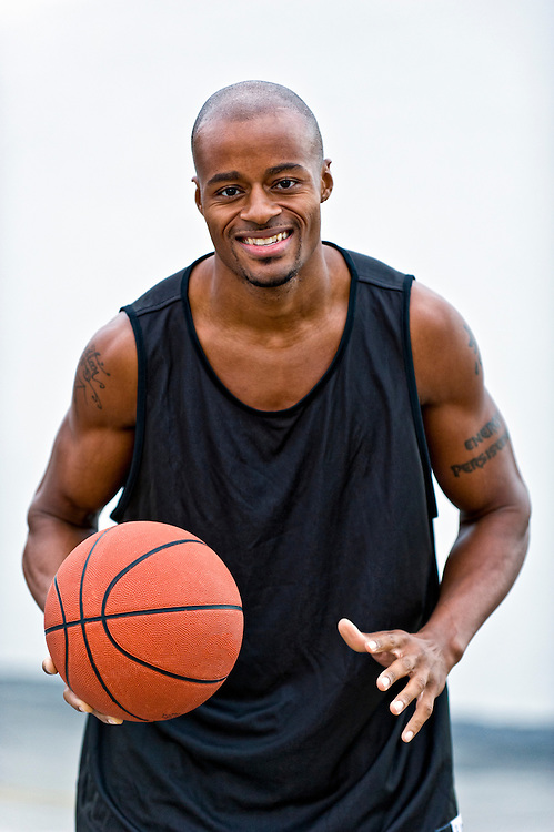 Young african american playing basketball in the street, smiling very happy.