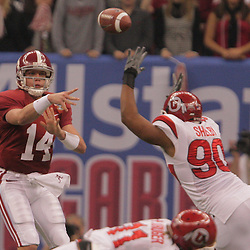2 January 2009: Alabama quarterback John Parker Wilson (14) throws past Utah defensive end Derrick Shelby (90) during the 75th annual All State Sugar Bowl  between the Utah Utes and the Alabama Crimson Tide at the Louisiana Superdome in New Orleans, LA.