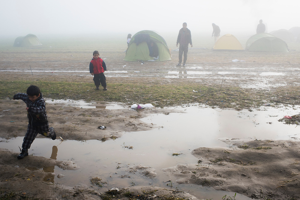 A child leaps over a puddle at a refugee camp on the Macedonian (FYROM) border on the morning of March 8, 2016 in Idomeni, Greece. Recent rains have soaked residents and turned the ground to mud in the camp.