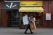 A delivery man struggles with a load of boxes and packages on a West End, on 4th March 2019, in London England.