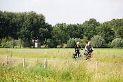 Bij Bunnik rijden fietsers door de weilanden.<br /> <br /> Near Bunnik cyclists ride at the pastures.