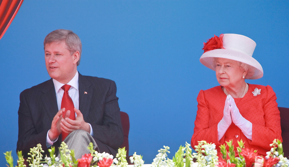 Queen Elizabeth II and Canadian Prime Minister Stephen Harper applaud during Canada Day celebrations on Parliament Hill in Ottawa, Ontario, July 1, 2010. The Queen is on a 9 day visit to Canada. <br /> AFP/GEOFF ROBINS/STR