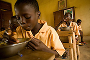Alhassan Alhassan, 13 (right) enjoys his lunch in a classroom at the Nyologu Primary School in the village of Nyologu, northern Ghana, on Wednesday June 6, 2007.