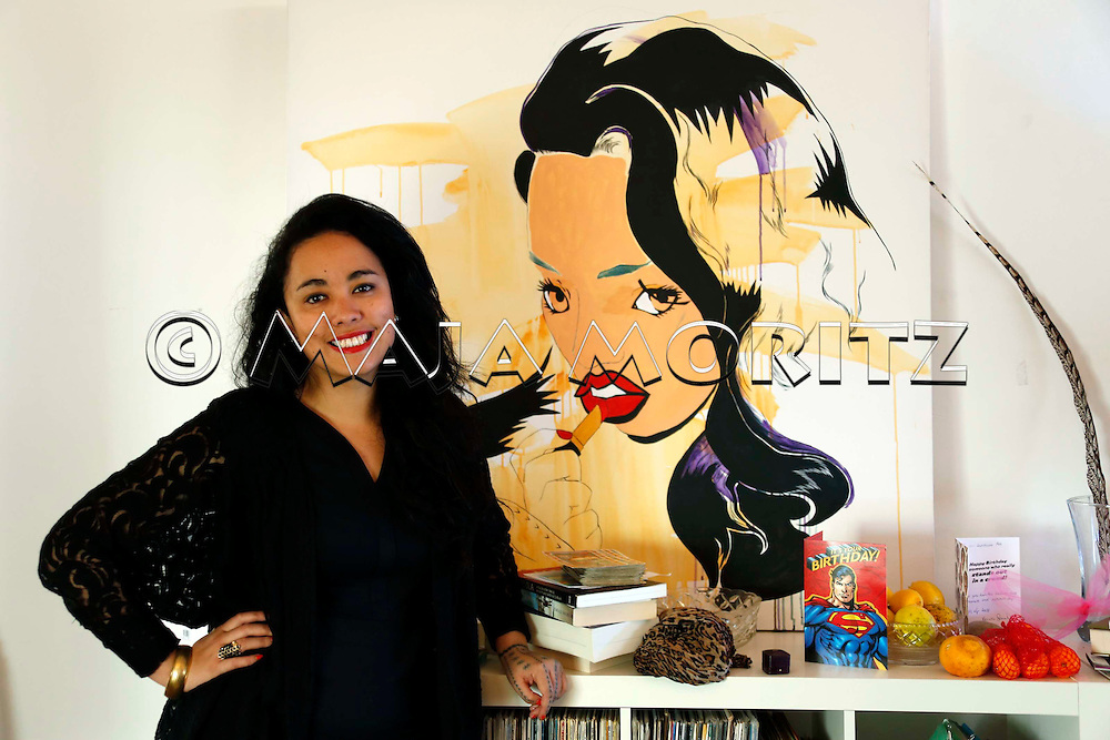 Young poet Courtney Meredith in front of a painting picturing herself in Auckland, New Zealand