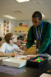 Stock photo of a student receiving help from his art teacher at Lovett Elementary in Houston Texas