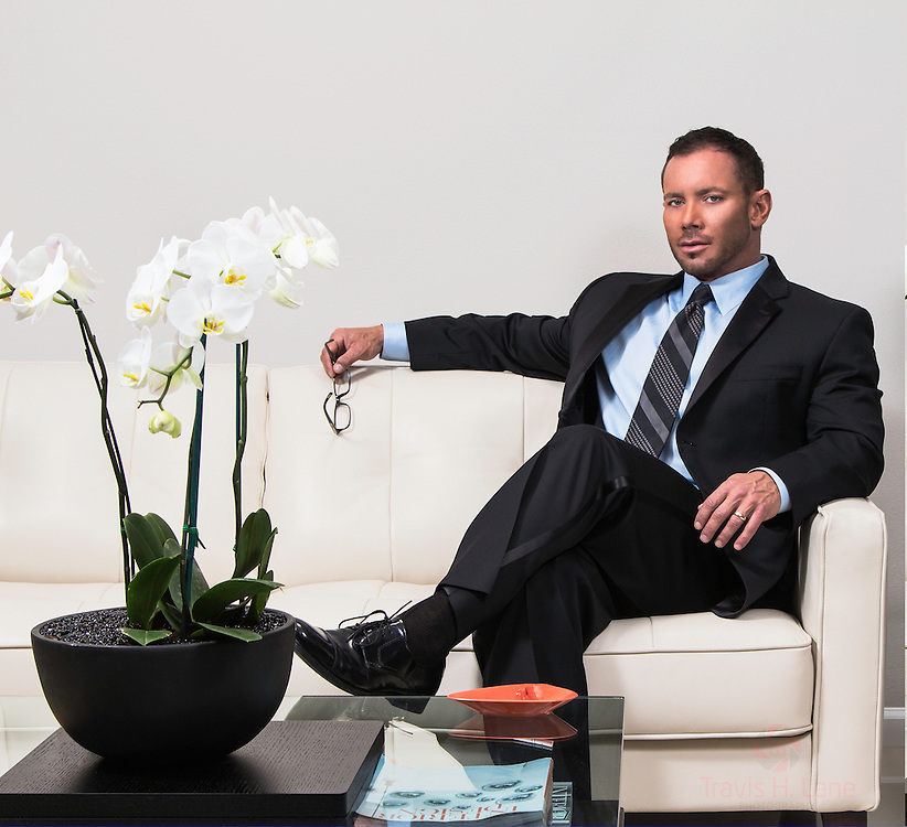 Scott Cullens sitting on a couch in a suit