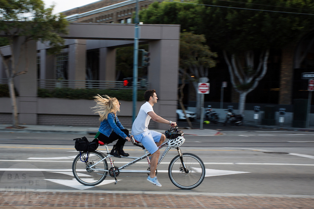 Een man en vrouw fietsen op een gehuurde tandem in San Francisco. De vrouw houdt haar voeten omhoog waardoor ze niet meetrapt. De Amerikaanse stad San Francisco aan de westkust is een van de grootste steden in Amerika en kenmerkt zich door de steile heuvels in de stad. Ondanks de heuvels wordt er steeds meer gefietst in de stad. <br /> <br /> A man and woman ride a rental tandem in San Francisco. The woman is not pedeling, she is holding her feet up. The US city of San Francisco on the west coast is one of the largest cities in America and is characterized by the steep hills in the city. Despite the hills more and more people cycle