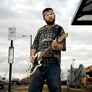 "Gary Creatsy plays his electric guitar along with the AC/DC Live double disk album he was listening to in his head phones while waiting for a bus to go home.  Although the guitar was not plugged him, Creatsy said he likes to play along to practice his chords.  He said it also is a good way to ""get your childness out"" and ""whined down with the day and have fun""."