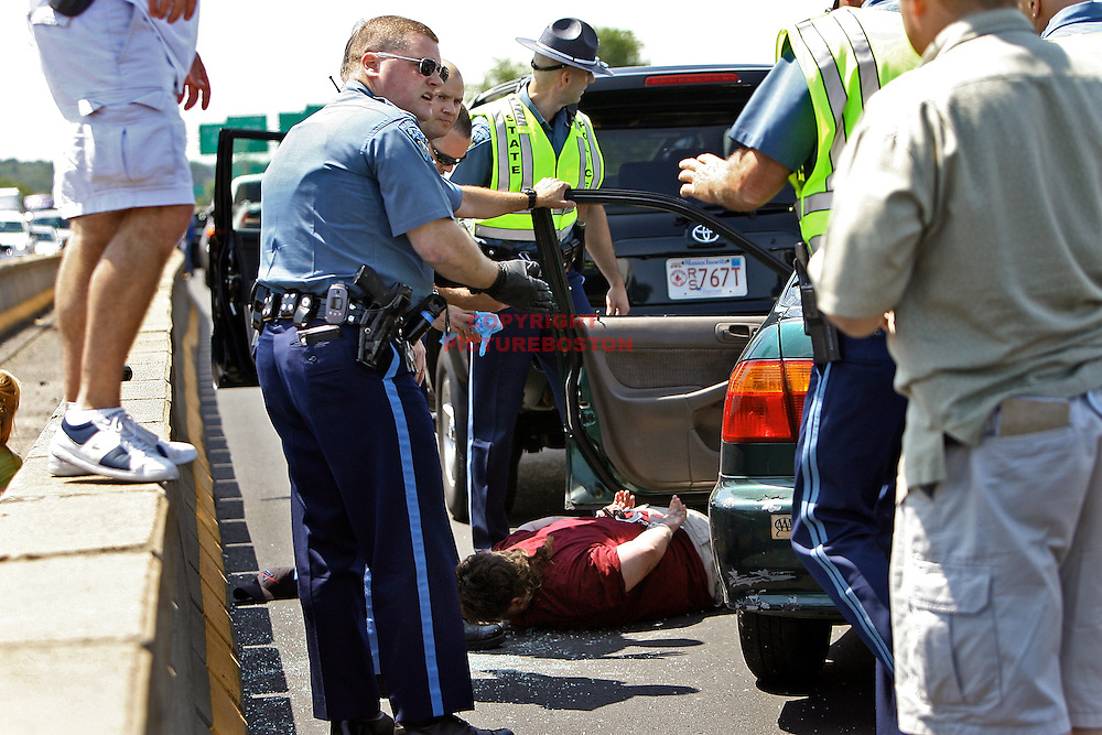 Police surround the driver as she lays on the highway.