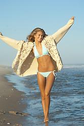 Young girl walking playfully along the beach in a bikini and sweater
