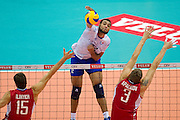 (C) Earvin Ngapeth from France attacks against (L) Dmitriy Ilinykh and (R) Nikolay Apalikov both from Russia during the 2013 CEV VELUX Volleyball European Championship match between Russia v France at Ergo Arena in Gdansk on September 25, 2013.<br /> <br /> Poland, Gdansk, September 25, 2013<br /> <br /> Picture also available in RAW (NEF) or TIFF format on special request.<br /> <br /> For editorial use only. Any commercial or promotional use requires permission.<br /> <br /> Mandatory credit:<br /> Photo by &copy; Adam Nurkiewicz / Mediasport