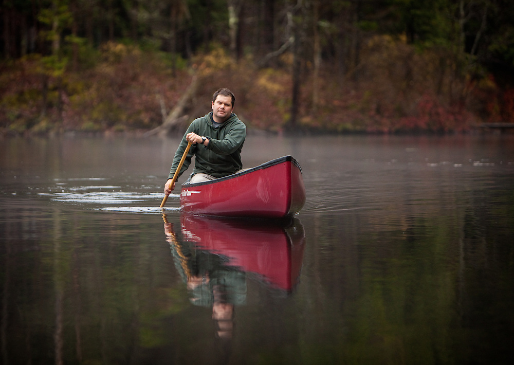 Man paddling a canoe on through fog on a quiet Adirondack pond, New York.