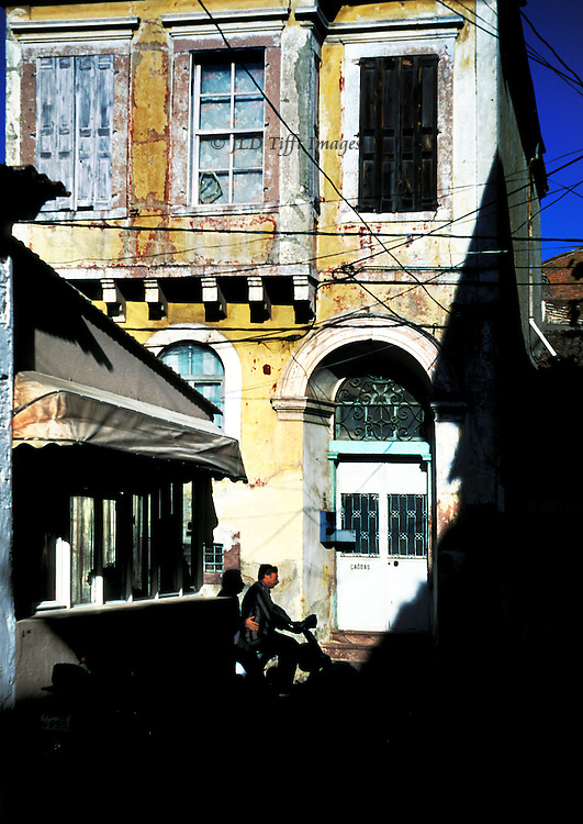 Sharp shadow partly covers an old but occupied house in Ayvalik, Turkey.  Bicyclist passes doorway with a newish mailbox.