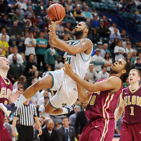 UNCW's Jordon Talley (4) soars to the net past Elon's Brian Dawkins (00) in the second half of the game at Trask Coliseum. Mike Spencer/StarNews