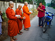 13 JANUARY 2019 - NAKHON PATHOM, THAILAND:  Female monks from Wat Songdhammakalyani chant after a man in the community gave the monks bottled water on their alms rounds. The Sangha Supreme Council, Thailand's governing body of Buddhist monks, bans the ordination of female monks, but hundreds of Thai women have gone abroad, mostly to Sri Lanka and India, to be ordained. There are about 270 women monks in Thailand and about 250,000 male monks. There are 7 monks and 6 novices at Wat Songdhammakalyani in Nakhon Pathom. It was the first temple in Thailand to have female monks. The temple opened 60 years ago and has always been a temple of women monks. Women can be ordained as novices in Thailand, but to be ordained as a full monk would require the participation of 10 female monks and 10 male monks, and male monks in Thailand are barred from participating in women's ordination ceremonies.    PHOTO BY JACK KURTZ