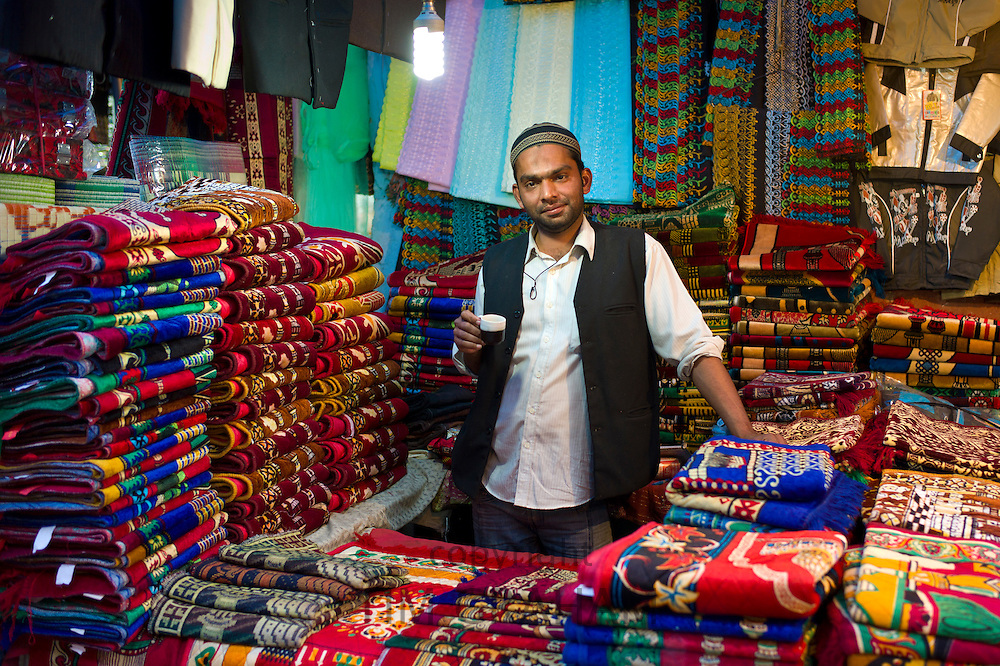 Stallholder drinking chai in shop selling prayer mats at muslim Meena Bazar, in Old Delhi, India
