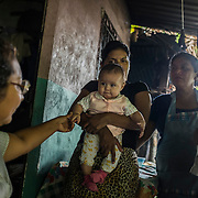 "Marta, 43 years old. Here in the house of her nephew, ex-maquila worker, now mother of a 4 months baby, here in their simple house in the forest inside the hills outside San Salvador. Marta  started working in a maquila in 2003. She works in the ""zona franca"" factories area of San Marcos, outside San Salvador, next to the highway to the airport. Recently she founded her own syndicate movement called SSINT to fight fir the rights of her co-workers. She earns approximately 7 US dollars per day, 250 per month, including the extra hours. She takes more than 2 hours to reach her work place from where she lives, in a ""Colonia"", controlled by the dangerous armed gang called MS."