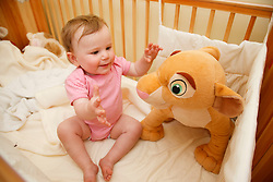 Baby into cot playing with soft toy