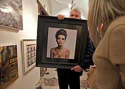© Licensed to London News Pictures. 19/04/2012. London, U.K..Kate Moss by Tony Briggs in the red gallery section being handled by staff..The Setting up of The Chelsea Art Fair in Chelsea Old Town Hall where Around 35 galleries and dealers offer modern British and contemporary art for sale, including paintings, drawings, etchings and sculptures. Represents 500 international artists, with art worth up to £20k. The fair runs from 19th April - 22nd April..Photo credit : Rich Bowen/LNP