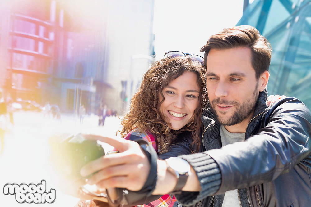 Portrait of young attractive man taking selfie with his girlfriend in the middle of the city