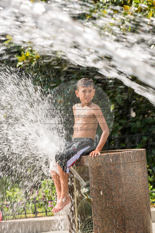 A young boy cools off in a public fountain at Waterfront Park as the southeast experiences a record setting heat wave June 22, 2015 in Charleston, South Carolina. Charleston has tied the historic record of 98-degrees (37 Celsius) and more hot weather is expected into next week.