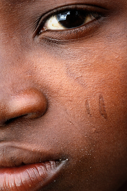 Benin, Tory February 26, 2006 - Man with tribal scarification on his face. It's the 2X5, It's the voodo Python. Scarification is used as a form of initiation into adulthood, beauty and a sign of a village, tribe, and clan.